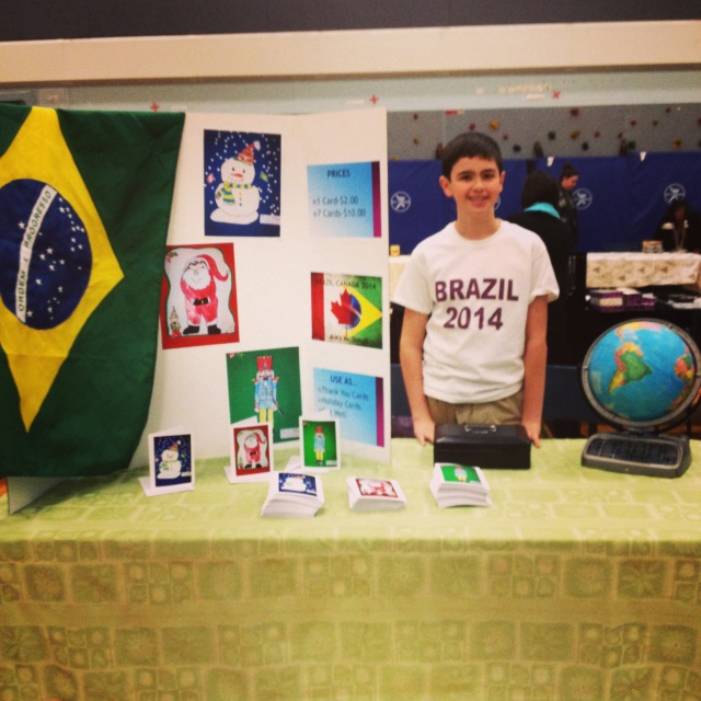 Alex selling his homemade Christmas cards at the craft fair to raise money for his trip.