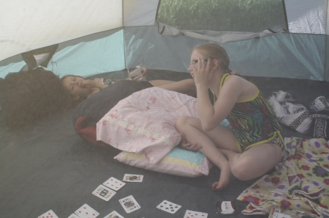 Playing cards and laughing together while catching some shade in the tent