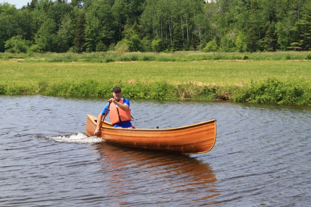 A happy & relaxed dad, paddling in his handmade canoe