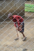 A boy sweeps the dirt in his yard